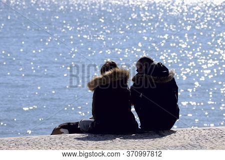 Couple Sitting By The Ocean On A Sunny Spring Day. A Man And A Woman In Jackets Are Resting On The P