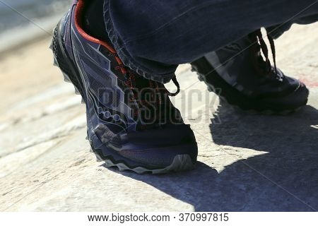 Legs In Sneakers Close Up. Sports Fashion For Shoes For Sports. Shadows Fall From The Legs In Sneake