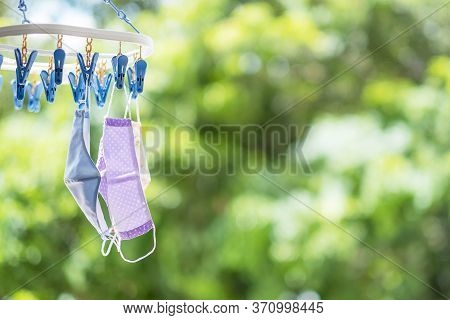 Fabric Face Mask Hang On Clothes Line On Green Nature Background. Protection Coronavirus (covid-19)