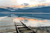 Sunset on Okanagan Lake viewed from an old dock with a boat launch running beside. poster