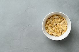 Raw Pumpkin Seeds In A White Bowl On A Gray Stone Background. Top View With Space For Text.