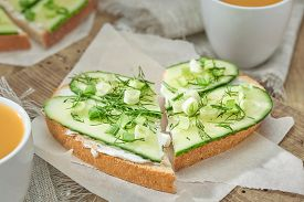 Sandwiches With Soft Cheese, Cucumber And Greens On The Wooden Cutting Board. Romantic Diet Breakfas