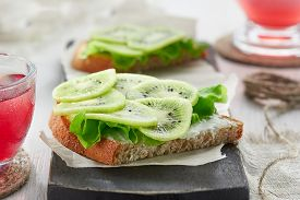 Diet Healthy Breakfast. Sandwiches With Soft Cheese, Salad And Kiwi On The Wooden Cutting Board.