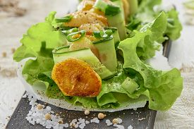 Sliced Fried Potatoes And Cucumber On Skewer On Leaf Of Green Lettuce On Wooden Board. Sea Salt Is S