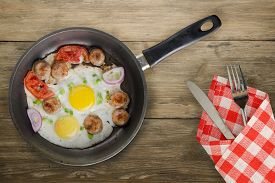 Fried Eggs With Sausage In A Frying Pan On Brown Wooden Background.fried Eggs With Fork And Knife To