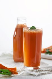 A Glass Of Freshly Squeezed Carrot Juice With Herbs On The Background Of A Bottle Of Juice.