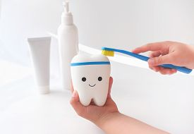 Little Girls Hands Cleaning Toy Tooth With Toothbrush. Oral Hygiene Concept. Cleaning Teeth And Dent