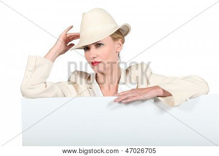Woman in a cream suit and trilby with a blank board ready for your message