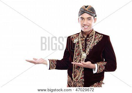 Feliz do homem vestindo tradicional de Java apresentando a área em branco
