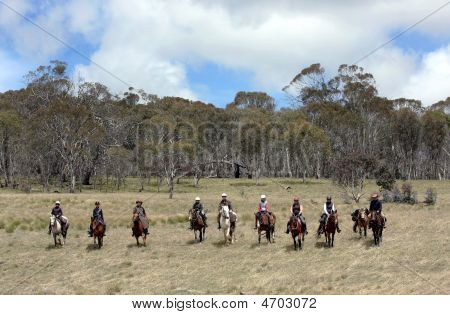 A group of horse riders in the Australian outback poster