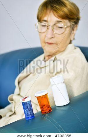 Elderly Woman Looking At Pill Bottles