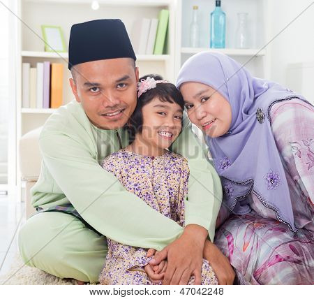 Muslim parents hugging child. Southeast Asian Malay family lifestyle. Happy smiling father mother and daughter.