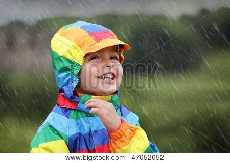 Little boy enjoying the rain dressed in a rainbow colored raincoat