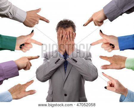 Hands pointing towards businessman holding head in hands concept for blame, accusations and bullying