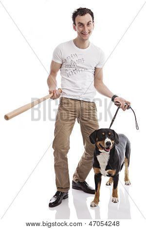 Young Caucasian man holding bat, with dog