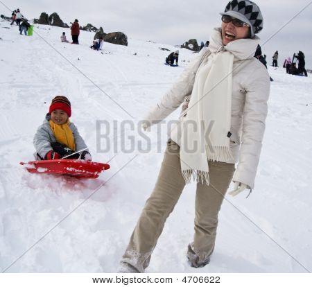 Smiling mother and son enjoy toboggan ride