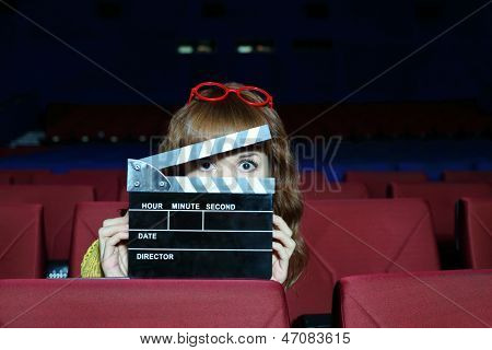 Happy beautiful woman looks through clap board in auditorium of movie theater.