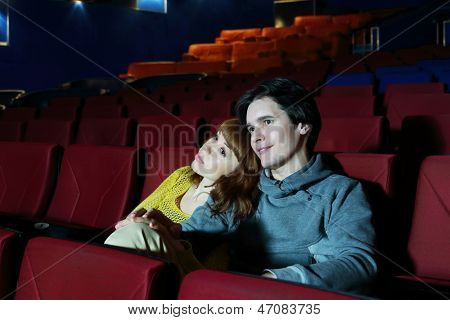 Young man and woman watch movie, embrace and smile in cinema theater.