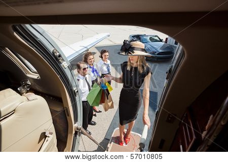 Full length of rich woman with shopping bags boarding private jet while pilot and airhostess looking at her