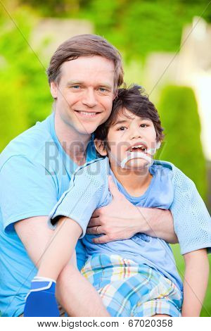 Handsome father sitting with smiling disabled seven year old son outdoors poster