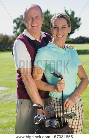 Golfing couple standing smiling at camera on a sunny day at the golf course