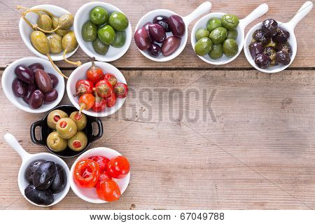 Border Of Olives And Peppers On A Wooden Counter