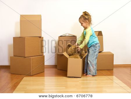 Excited Little Girl Unpacking In Her New Home