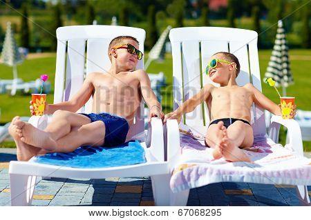 Teenage Boys Relaxing On Sunbeds In Waterpark