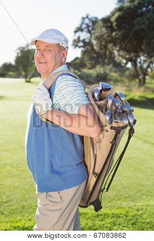 Golfer standing holding his golf bag smiling at camera on a sunny day at the golf course