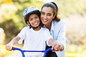 cheerful indian mother teaching her son to ride a bike poster