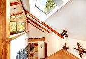 Log cabin house interior. View of ceiling with beams and velux window from loft office staircase poster