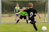 Goalkeeper and penalty kicker in the midst of a penalty kick during a youth soccer match. Focus is on the kicker. poster