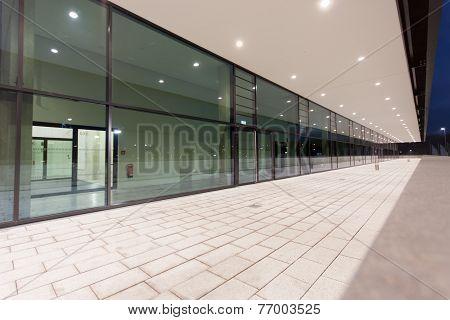 Illuminated Pedestrian Passage Perspective Along Glass Building Facade
