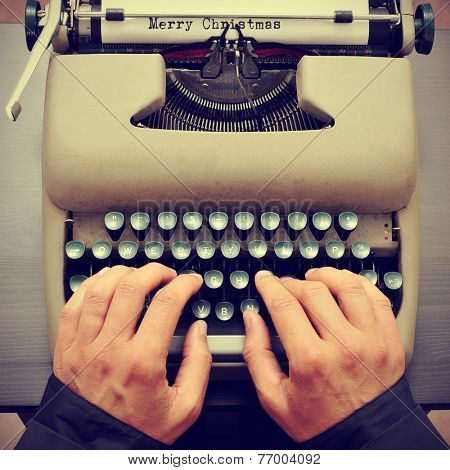 a young man typewriting the text merry christmas in a paper sheet on an old typewriter, with a retro effect