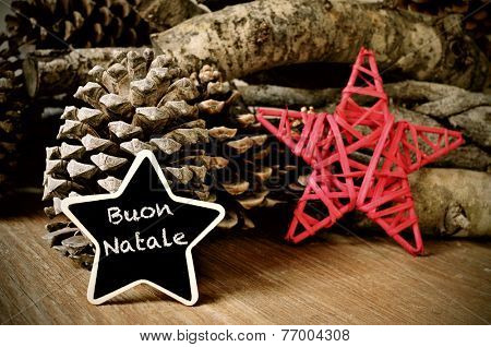 the text buon natale, merry christmas written in italian in a star-shaped blackboard, and a christmas star, some pinecones and a pile of logs in the background