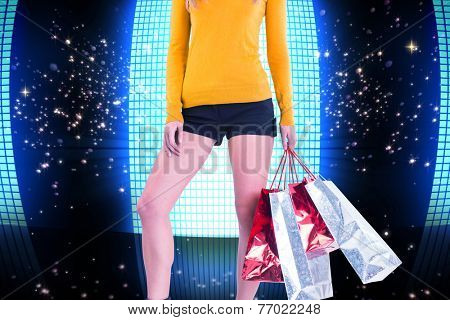 Stylish woman with shopping bags against glittering screen on black background