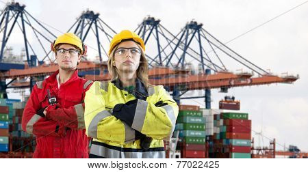 Two proud looking dockers, wearing safety attire with their arms crossed standing in front of a huge container ship being unloaded in an industrial harbour.