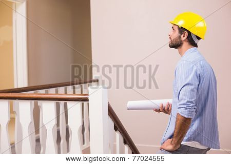 Casual architect walking up the stairs in a new house