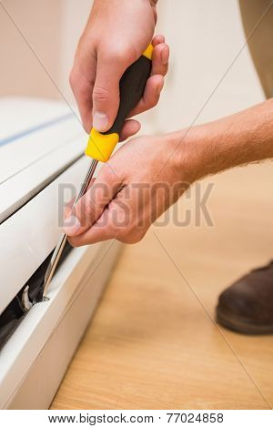 Handyman fixing an air conditioning in a new house poster