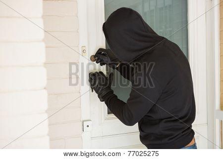 Burglar breaking open the door of someones home