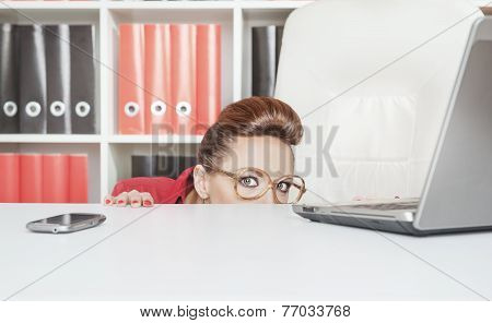 Business woman with glasses hiding behind table and afraid poster