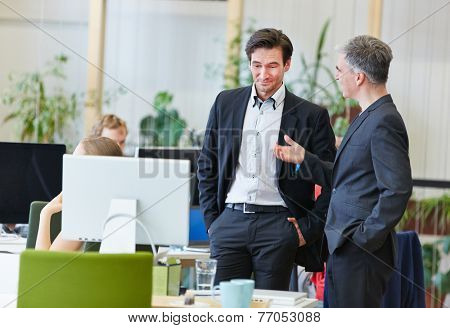 Two business men in office talking to each other