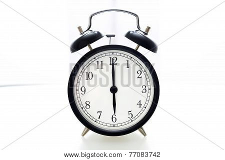 Oldfashioned black glossy alarm clock showing 6 o'clock poster