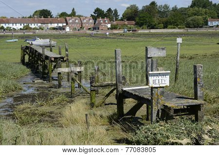 Old disused and broken wooden jetty at Bosham in Chichester Harbour. West Sussex. England. Low tide with exposed seaweed poster