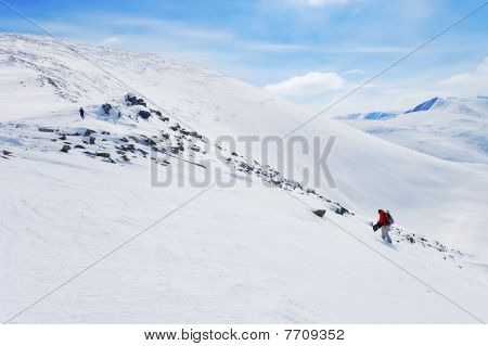 Backcountry snowboarder climbing up by the mountain ridge