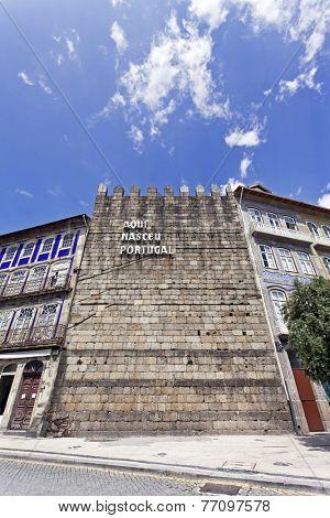 Guimaraes, Portugal. April 25, 2014: The iconic Guimaraes Castle Wall with the inscription Aqui Nasceu Portugal (Portugal was born here). Guimaraes, Portugal. Unesco World Heritage Site.