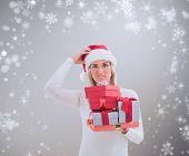 Confused blonde in santa hat holding gifts against grey vignette poster