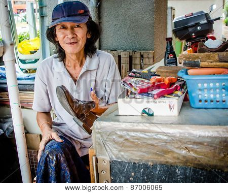 Old woman at her shoe shine stand in Singapore