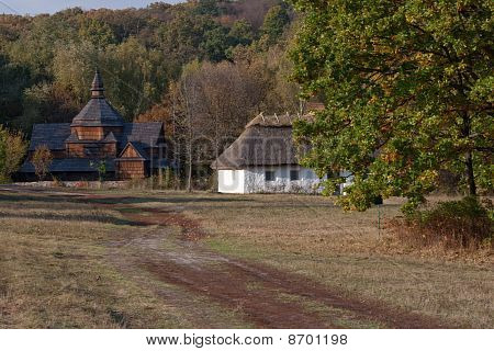 Autumnal Village Scenery. Wooden Church And Hut.