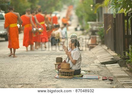 People giving alms to buddhist monks